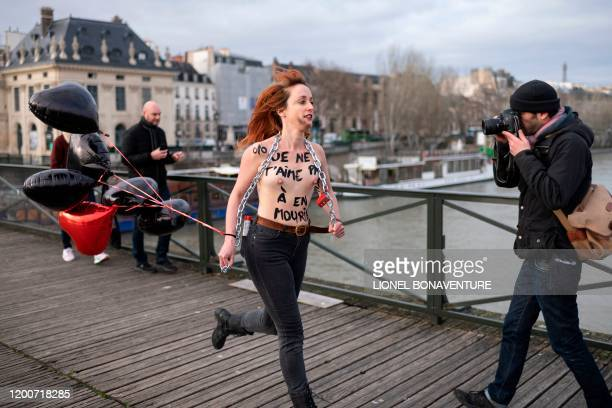 Graphic content / A man takes a picture as a member of the feminist movement Femen is chained on the pont des Arts in Paris on February 14 2020 on...