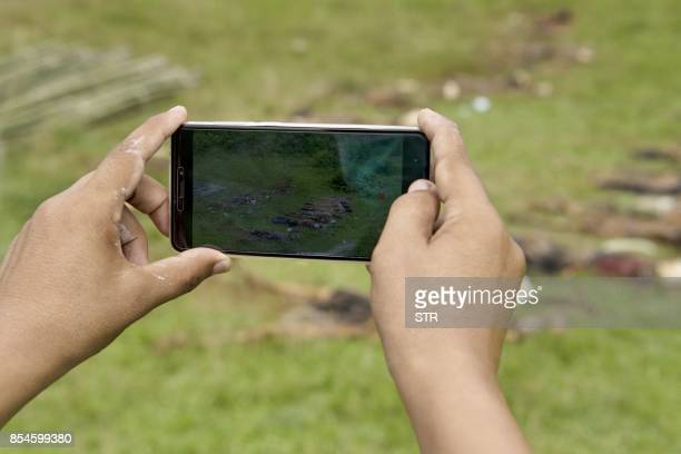 Graphic content / A man takes photos with a mobile phone of the dead bodies in Yebawkya village Maungdaw on September 27 2017 Myanmar's army said on...