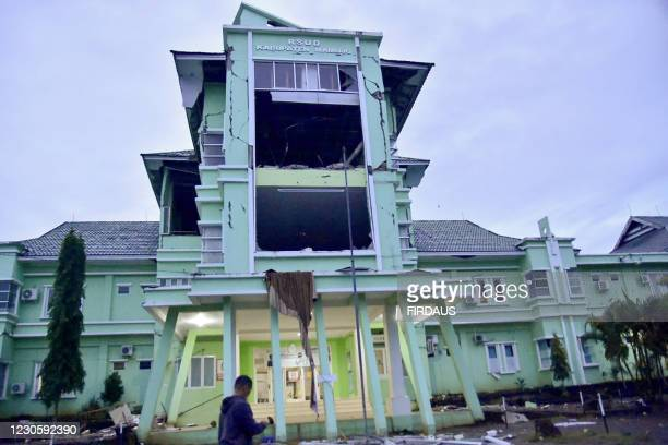 Graphic content / A man walks by a damaged hospital in Mamuju city on January 15 after a 6.2-magnitude earthquake rocked Indonesia's Sulawesi island.