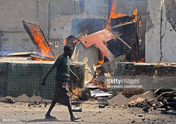 Graphic content / A man walks past the scene of a suicide attack in the Somali capital Mogadishu on July 31 2016 Six people were killed in a gun and...