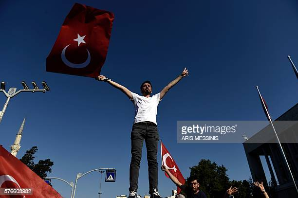 Graphic content / A man waves a Turkish flag during a demonstration in Istanbul in support the government on July 16 following a failed coup attempt...