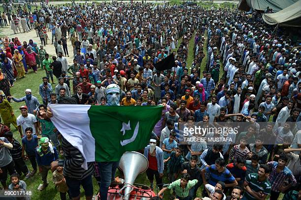 Graphic content / A masked Kashmiri mourner holds up a Pakistani flag as others shout antiIndian and profreedom slogans during the funeral of four...