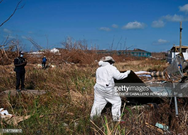 Graphic content / A member of a Bahamian body recovery team lifts a plywood sheet to uncover a body in Marsh Harbour Bahamas on September 10 one week...