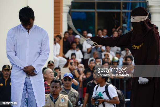 Graphic content / A member of Indonesia's Sharia police whips a man accused of having gay sex during a public caning ceremony outside a mosque in...