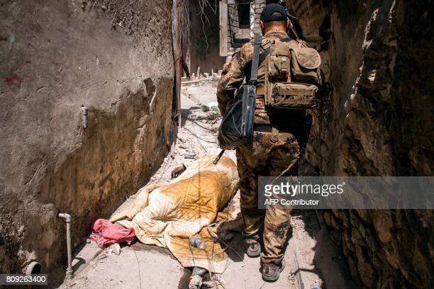 Graphic content / A member of Iraq's CounterTerrorism Service walks by a dead body in the Old City of Mosul on July 5 during the government forces'...