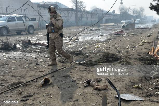 Graphic content / A member of the Afghan security forces looks at a severed leg at the site of a suicide bomb attack outside a British security...