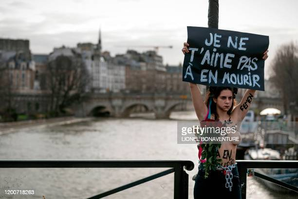 Graphic content / A member of the feminist movement Femen holds a banner reading I don't love you untill dying as she is chained on the pont des Arts...