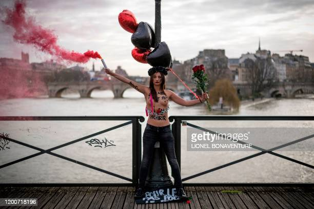 Graphic content / A member of the feminist movement Femen holds flare as she is chained on the pont des Arts in Paris on February 14 2020 on...