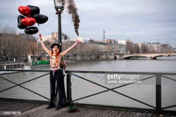 Graphic content / A member of the feminist movement Femen is chained on the pont des Arts in Paris on February 14 2020 on Valentine's day during an...