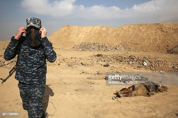 Graphic content / A member of the Iraqi forces checks a mass grave they discovered in the Hamam alAlil area on November 7 2016 after they recaptured...
