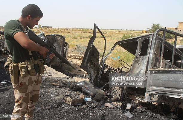 Graphic content / A member of the Iraqi government forces stands near a body lying on the road next to a charred vehicle southwest of Fallujah on...