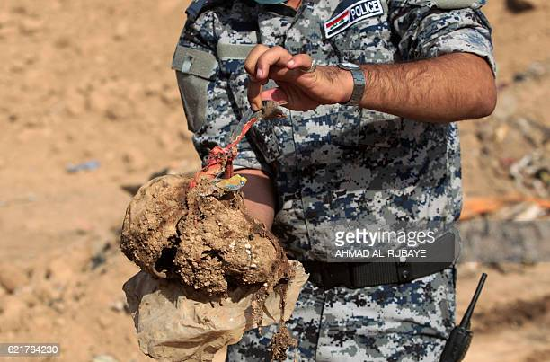 Graphic content / A member of the Iraqi police holds a skull dug up from a mass grave they discovered in the Hamam alAlil area on November 7 2016...