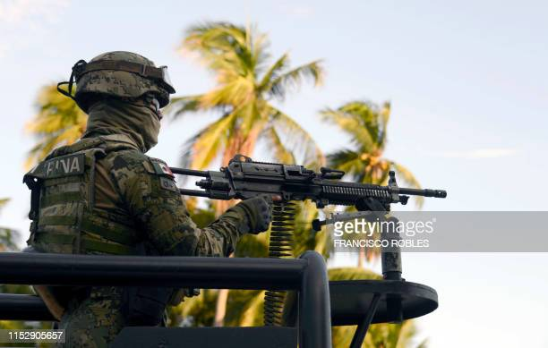 Graphic content / A member of the Mexican Navy patrols near the site where the bodies of two car washers were found dead in the Mexican resort town...