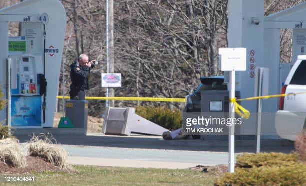 Graphic content / A member of the Royal Canadian Mounted Police forensic identification unit photographs the body of a deceased man after a deadly...