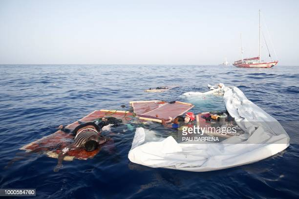 Graphic content / A member of the Spanish NGO Proactiva Open Arms rescues a woman from a sinking boat as another lies dead on what is left of the...
