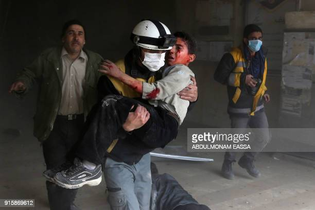 Graphic content / A member of the Syrian civil defence carries a wounded child from the rubble after a reported regime air strike in the rebelheld...