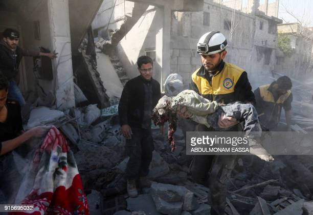 Graphic content / A member of the Syrian civil defence carries the body of a child from the rubble after a reported regime air strike in the...
