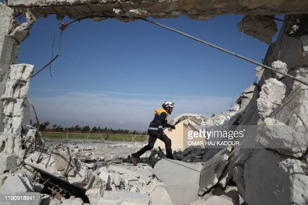 Graphic content / A member of the Syrian Civil Defence known as the White Helmets, rushes to help victims following an air strike by pro-regime...