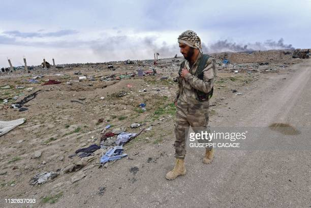 Graphic content / A member of the Syrian Democratic Forces walks along a road in the village of Baghouz in Syria's eastern Deir Ezzor province near...