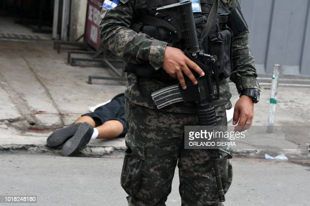 Graphic content / A military policeman remains next to the corpse of a vendor at a crime scene in Comayaguela Honduras on August 17 2018 In the...