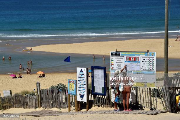 Graphic content / A naked couple look at the weather forecast as they arrive at the beach of the Arnaoutchot naturist camping on June 26 2018 in...