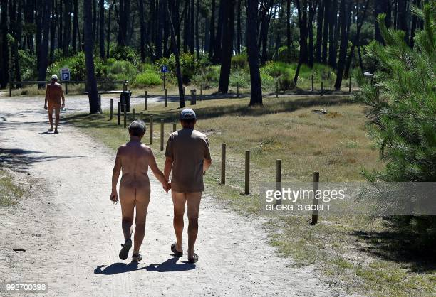 Graphic content / A naked couple walk on a path at the Arnaoutchot naturist camping on June 26 2018 in VielleSaintGirons southwestern France...