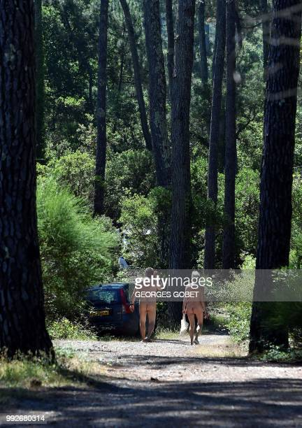 Graphic content / A naked couple walks on a path at the Arnaoutchot naturist camping on June 26 2018 in VielleSaintGirons southwestern France...