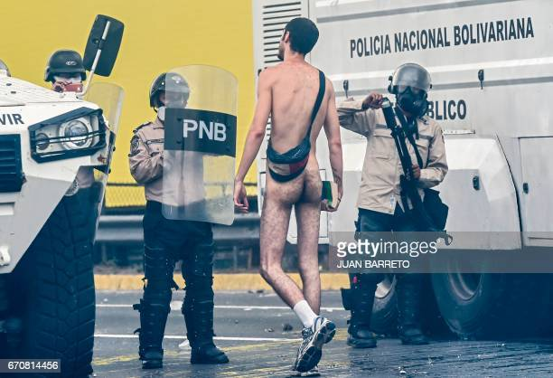 Graphic content / A naked demonstrator remonstrates with riot police during a protest against Venezuelan President Nicolas Maduro in Caracas on April...