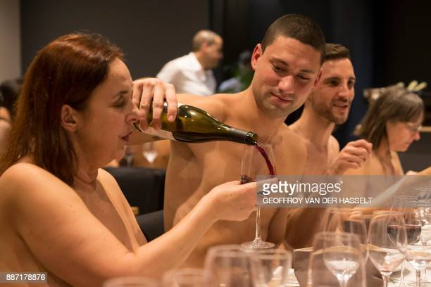 Graphic content / A nude diner fills wine for another at the newly opened nudist restaurant o'naturel in Paris on December 5 2017 Leave your coats...