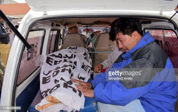 Graphic content / A Pakistani relative sits next to the dead body of a blast victim while being carried from the hospital in an ambulance following a...