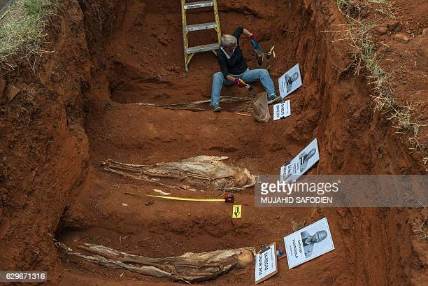 Graphic content / A person works on the exhumation of 14 bodies of political prisoners executed in 1964 during the apartheid on December 14 2016 at...