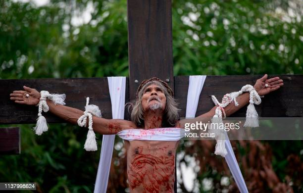 Graphic content / A Philippine Christian devotee is nailed to a cross during a reenactment of the Crucifixion of Christ during Good Friday ahead of...