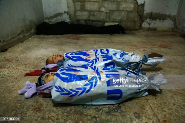Graphic content / A picture taken at a makeshift morgue in Douma in Syria's rebelheld Eastern Ghouta region on the outskirts of Damascus on March 4...