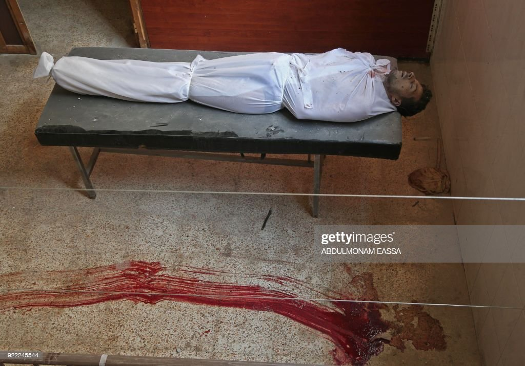 Graphic content / A picture taken on February 21, 2018 shows the body of a Syrian youth prepared for burial lying on a bed next to blood stains on the floor, at a make-shift clinic in the rebel-held enclave of Hamouria in the Eastern Ghouta near Damascus, after he was killed in a reported regime air strike. /