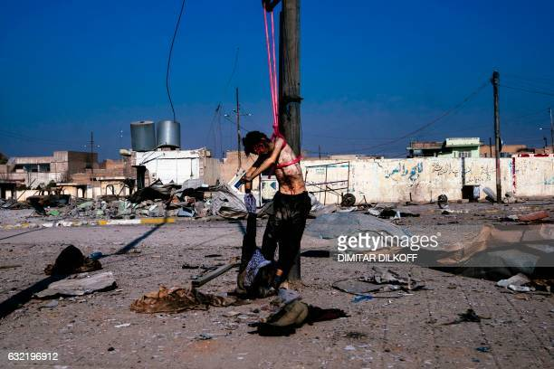 Graphic content / A picture taken on January 20 shows a dead body hanging from an electricity post in eastern Mosul during an ongoing military...