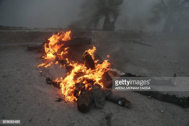 Graphic content / A picture taken on March 7 2018 shows the burning bodies of two men who were killed as they were riding a motorbike during the...