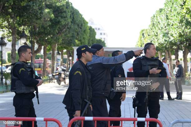 Graphic content / A picture taken on October 29 shows Tunisian police gathering at the site of a suicide attack in the centre of the Tunisian capital...