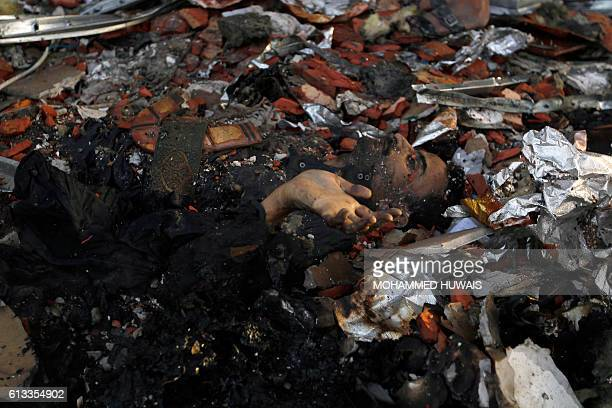 Graphic content / A picture taken on October 8 2016 shows a charred body amid the destruction of a funeral hall following reported airstrikes by...