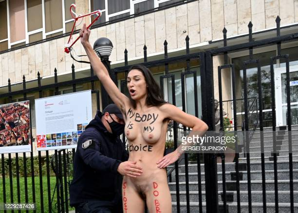Graphic content / A police officer detains a FEMEN naked activist during an action at the Polish embassy in Kiev on October 26, 2020 in support of...