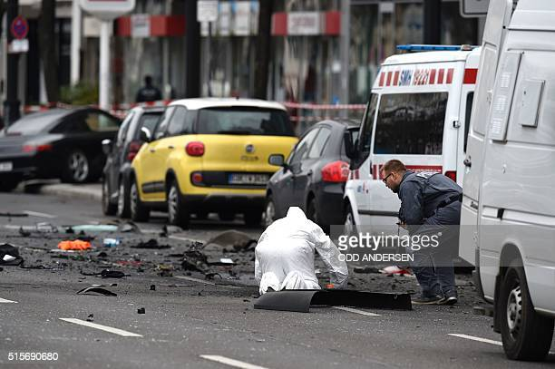Graphic content / A policeman and a forensic staff work at debris near the wreckage of a car after a blast caused by an explosive device killed its...