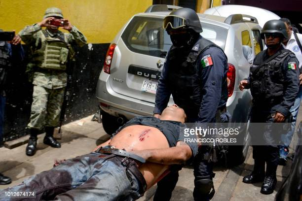 Graphic content / A policeman carries one of three wounded men after an attack at a mechanic's shop in Acapulco Guerrero State Mexico on July 31 2018...