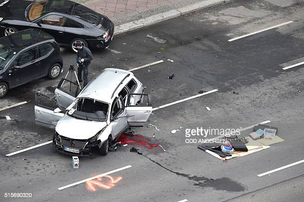 Graphic content / A policeman stands near the wreckage of a car after a blast caused by an explosive device killed its driver travelling down a...
