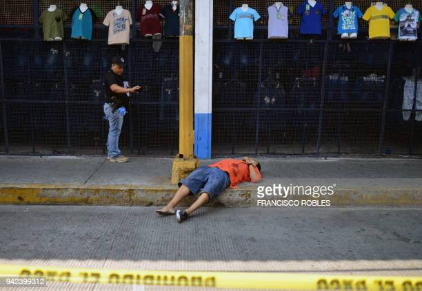 Graphic content / A prosecutor's office agent takes pictures of the corpse of a man executed by armed men who chased him off along Cuauhtemoc Avenue...