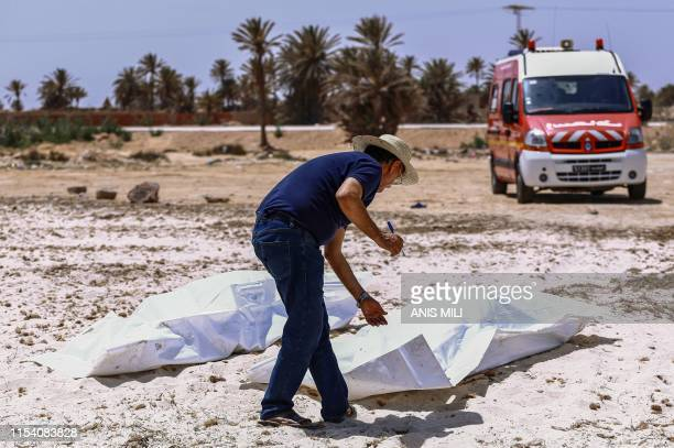 Graphic content / A representative of the Tunisian Red Crescent association checks bodies recovered from a boat carrying 86 migrants that capsized...