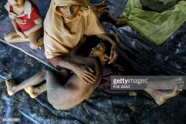 Graphic content / A Rohingya refugee from Myanmar's Rakhine state holds a child as she sits in a makeshift shelter after arriving at a refugee camp...