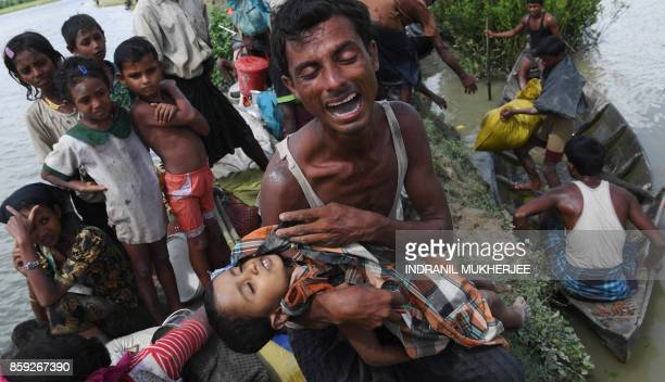 Graphic content / A Rohingya refugee reacts while holding his dead son after crossing the Naf river from Myanmar into Bangladesh in Whaikhyang on...