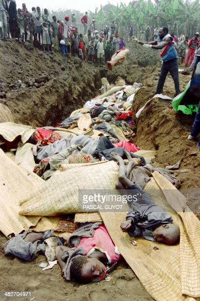 A Rwandan man throws the body of a baby wrapped up in sheets into a mass grave on July 21 1994 in Goma According to Medecin Sans Frontiere...