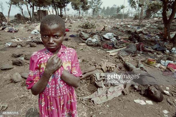 A Rwandan refugee stands on July 17 1994 among the corpses of over 100 of her compatriots who were trampled in the eastern Zairean border of Goma by...