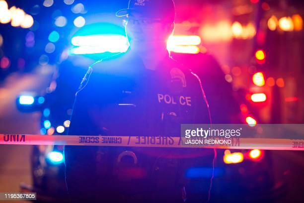 Graphic content / A Seattle Police officer is pictured at the scene of a shooting that left one person dead and seven injured, including a child, in...