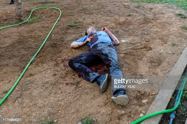 Graphic content / A severely injured officer lies on the ground in the garden of a Turkish government building in Akcakale near the Turkish border...